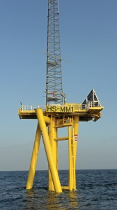 An example of a twisted jacket turbine foundation.  The wind turbine structure would be mounted atop the yellow foundation base where the girding is in this photo.  The unique foundation design came about through a competitive grant program sponsored by the Carbon Trust to encourage wind power development.  Built ashore, multiple units can be transported together providing significant cost savings. (Carbon Trust photo)