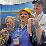 From left, Angela Sanfilippo, longtime president of the Gloucester Fishermen's Wives Association, Gloucester Mayor Sefatia Romeo Theken, and Todd Snopkowski of SnapChef – whose team helped the Fishermen's Wives prepare vats of their famous redfish soup served at Seafood Expo in Boston. Several Gloucester seafood companies donated the 125 pounds of redfish that went into the soup. Romeo Theken displays one redfish. Susan Pollack photos