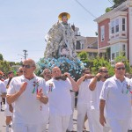 The Statue of St. Peter, draped in dollar bills and adorned with flowers, leads the procession through the city during Gloucester's St. Peter's fiesta.  (Susan Pollack photo)