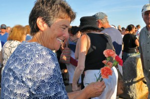 Greenlaw handed out orange and red carnations, which Gloucester fishing families ceremoniously tossed into Gloucester Harbor. (Susan Pollack photo)