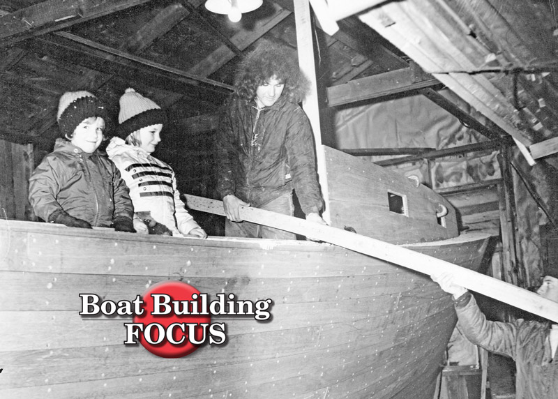 Brian, Bruce Jr., and Bruce Sr. receiving a plank from Leonard Eugley.  (Red Boutilier photo, courtesy Farrin's Boatshop)