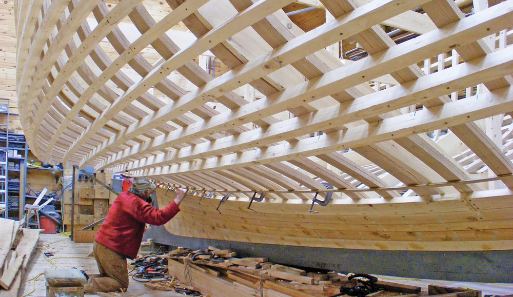 Richard Stanley at work beneath the 38-footer underway in his Bass Harbor shop.  (Brian Robbins photo)