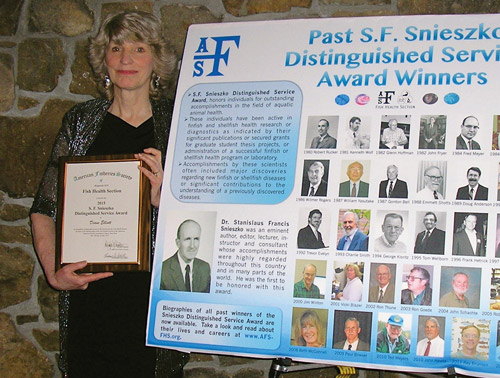 Diane Elliott, the 2015 recipient of the prestigious S.F. Snieszko Distinguished Service Award, with the Fish Health Section's poster showing previous award winners. Janice Plante photo